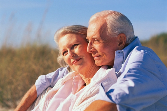 Older Couple Sitting Together at Beach